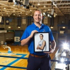 Andrew Atman, BS '08, holding a picture of his younger self playing basket.