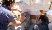 Photo of Michael Wells and Paul Pavia moving stone.