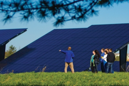 Students and a professor inspecting solar panels.