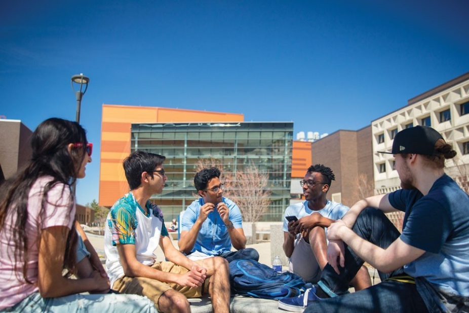 Students talking outside of Davis Hall on a sunny day.