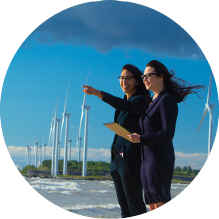 two women with large windmills in the background