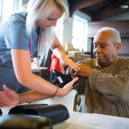 A nursing student helps an elderly man adjust his blood pressure cuff.