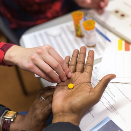 A pharmacist places a yellow pill on another person's hand to examine.