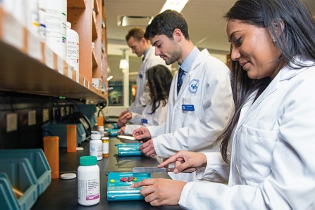 Pharmacy students count out pills using a pill tray.