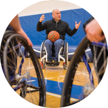 man in wheelchair holding a basketball