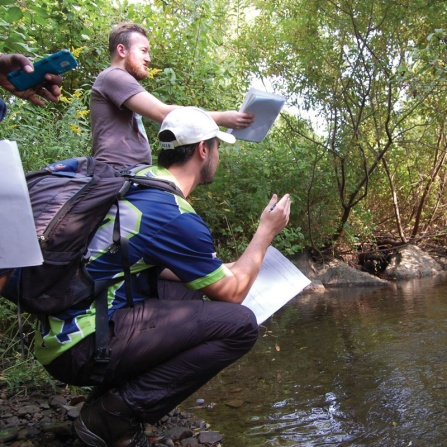 Students surveying an area by a creek.