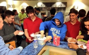 students gathered around a counter top serving themselves ice cream.