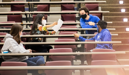 four students wearing face masks in classroom.