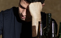 depressed man among alcohol bottles