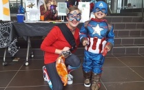 Community Research Facilitator Megan Wilson-Crowley and another masked superhero at the fair