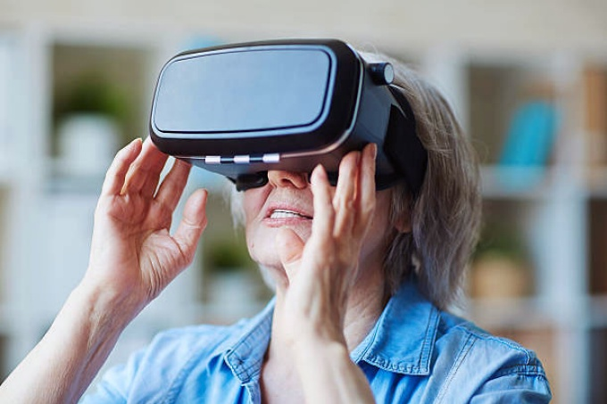 an elderly female wears virtual reality goggles.