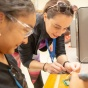 A student from Buffalo Public Schools starts to build her own simple smartphone using a Raspberry Pi computer circuit board as part of a camp program.