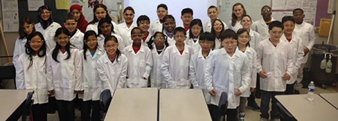 A large group of young students in lab gear stand together smiling .