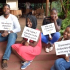 Ugandans holding signs related to diabetes awareness.