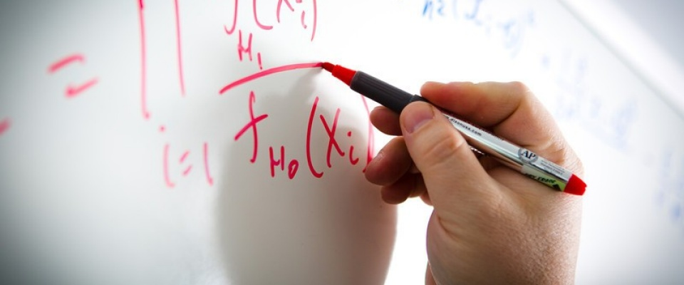 hand draws equation on board.
