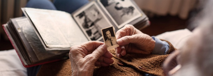 Elderly male looking at old photographs.
