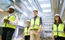 Students in hard hats and safety vests touring the building