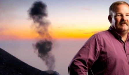 Greg Valentine stands before a volcano emitting a slender plume