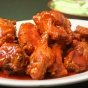 A photo showing a plate of sauce-covered Buffalo chicken wings.