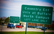 Green and white road sign displaying directions to UB's North Campus
