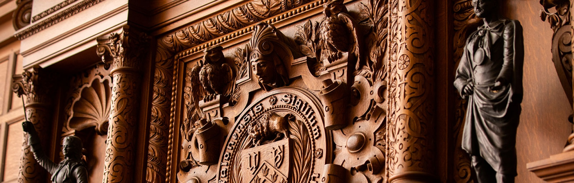 Detail of heavily carved wooden mantle at the Health Sciences Library main reading room.