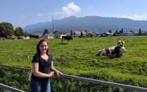 Patricia Johnson stands in front of a green pasture where cows sit on the grass, on a sunny day.