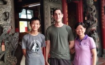 Conor McMahon standing between two members of his host family in Taiwan.