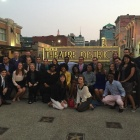 A group of people in front of the Buffalo Theatre District sign. .