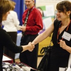 Two women shaking hands at a trade show.