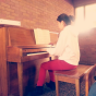 Esther on piano with sunlight
