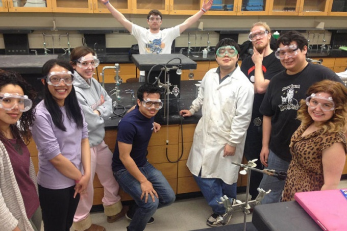 Students in a research lab smiling.