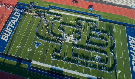 Hundreds of UB students form a human UB logo.