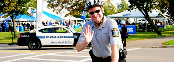 UB police officer waving on a bicycle