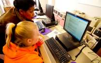 An academic adviser helps a student in a computer lab.