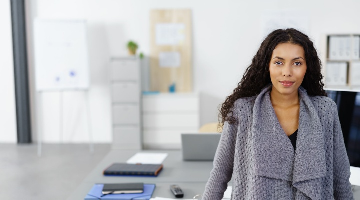 Woman stands in an office.