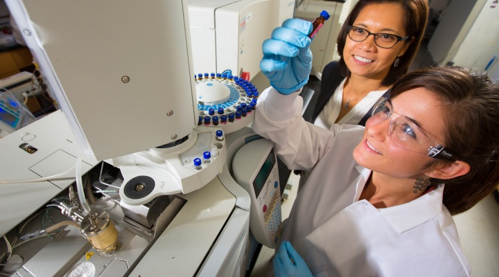 student and professor conduct experiment in a lab.