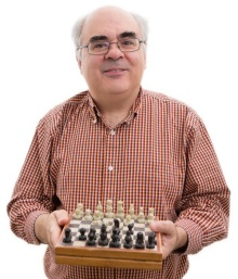 Ken Regan holding a chess board.