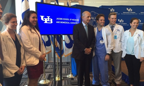 UB Council Chairman Jeremy M. Jacobs and group of UB medical students in front of a digital screen displaying the newly named Jacobs School of Medicine and Biomedical Sciences