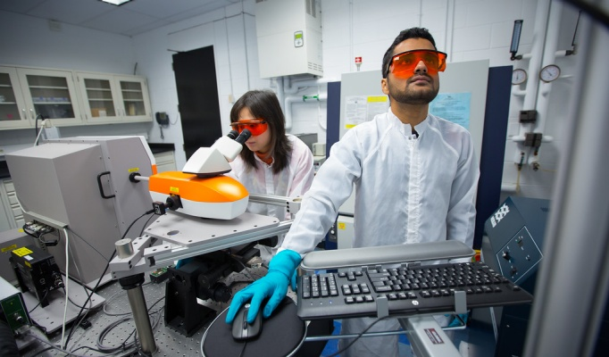Researchers in lab using machines.
