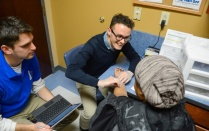 Daryl Spak, left, a second-year medical student, and first-year student Patrick Salemme examine a patient at the Lighthouse clinic. Photo: Nancy J. Parisi - See more at: http://www.buffalo.edu/ubreporter/stories.host.html/content/shared/university/news/ub-reporter-articles/stories/2016/02/lighthouse_clinic.detail.html#sthash.t4Z49Oze.dpuf