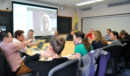 Valerie Nesset, Ph. D., sits around a large table with the Faculty IT Liaison group on the 5th floor of Baldy Hall