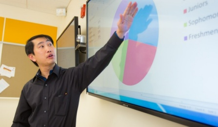An instructor points to information from a pie chart being presented on a large screen.