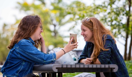Two students laughing outside with phone