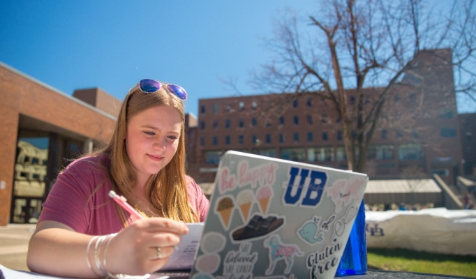 A student works outside on a laptop.