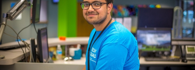 A smiling UB Tech Squad representative at a service desk.