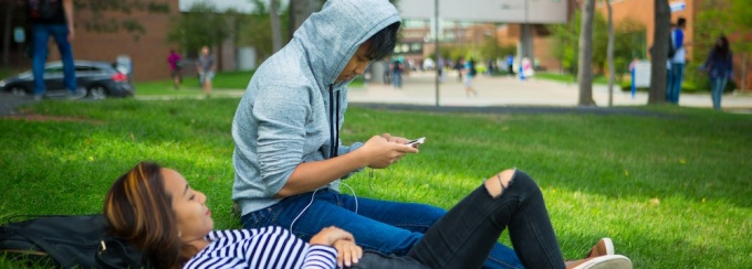 Two students sit in the grass outside on North Campus. One is looking at a smartphone.