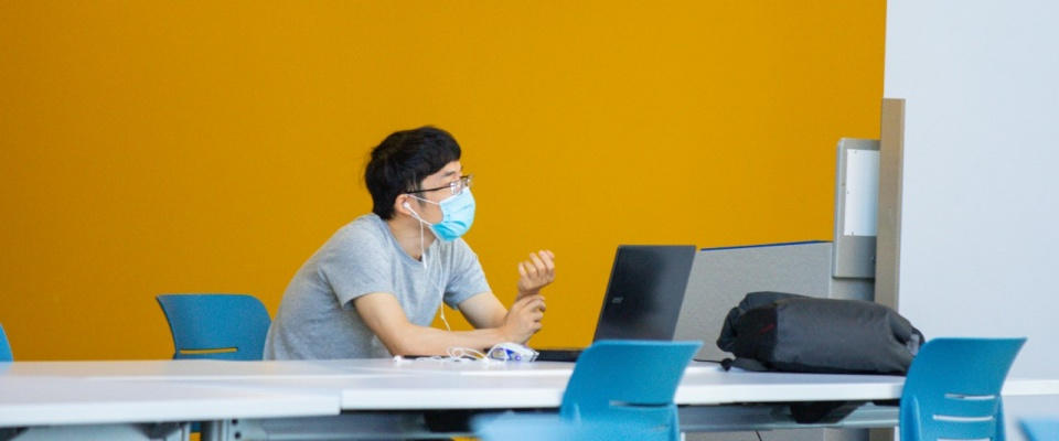 A UB student wearing a mask works on a laptop in a public study space on UB's north campus.