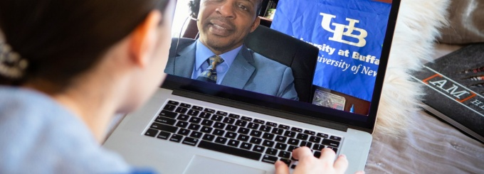 Glenn Taplin, with Admissions, is photographed speaking with an unkown student via a video conference in April 2020. This is a photo illustration.