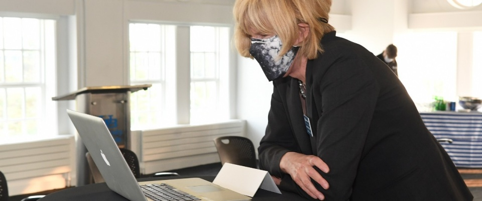 A woman in a mask participates in a Zoom meeting on her laptop.