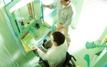 A man in a wheelchairin front of a sink, with another man standing beside him.